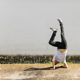 Young male dancer doing handstand against gray wall