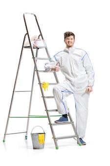 Giovane pittura maschio del decoratore con un rullo di pittura e una scala isolata sulla parete bianca.