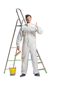 Young male decorator painting with a paint roller and a ladder isolated on white wall.