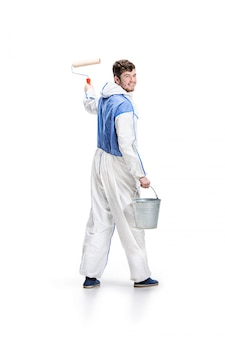 Young male decorator painting with a paint roller on white wall.