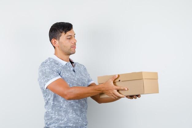 Tシャツで段ボール箱を配達し、責任があるように見える若い男性