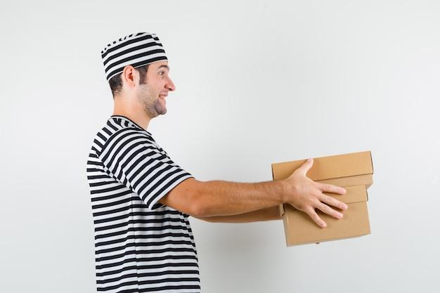 Tシャツ、帽子、陽気に見える段ボール箱を配達する若い男性。 。