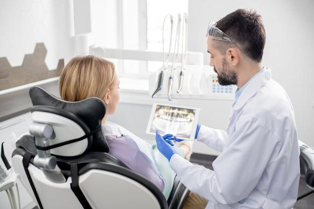 Молодой стоматолог в перчатках и белом халате объясняет пациенту все проблемы с зубами, показывая рентген в планшете