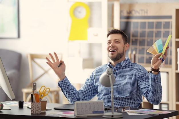 Молодой дизайнер мужского пола, работающий в офисе