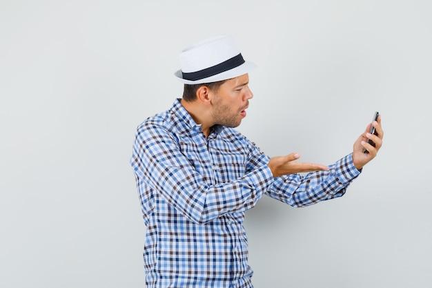 Giovane maschio che discute qualcosa sulla chat video in camicia a quadri