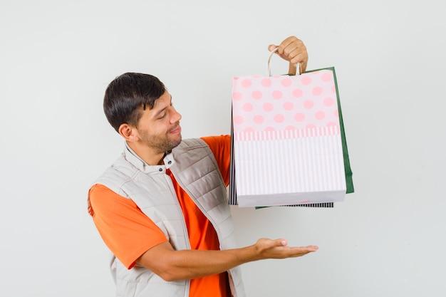 Tシャツ、ジャケット、陽気に見える、正面図で買い物袋を表示する若い男性。