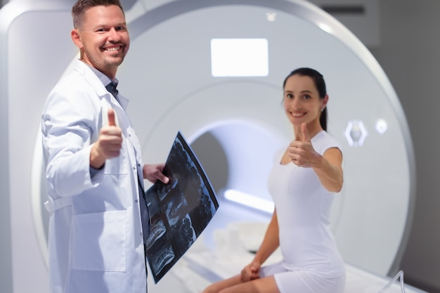 若い男性医師と女性患者がmri室の磁気共鳴画像法で親指を立てる