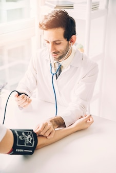 Young male doctor checking blood pressure of patient in clinic