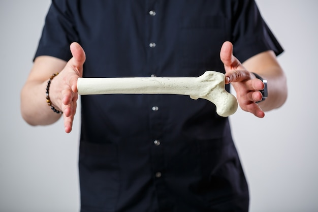 검은 수술복을 입은 젊은 남성 의사 수석 의사. 클로즈업 초상화입니다. 그의 손에 대퇴골을 보유합니다. 흰색 배경에 고립.