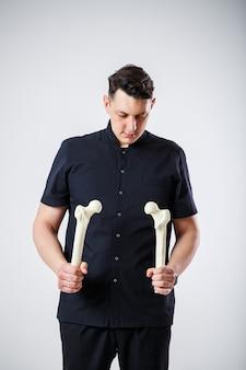 黒の手術服を着た若い男性医師主治医。クローズアップの肖像画。大腿骨を手に持っています。白い背景で隔離。