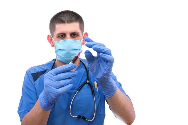 Молодой мужской доктор, исследующий шприц с кровью пациента, изолированные на белом фоне.