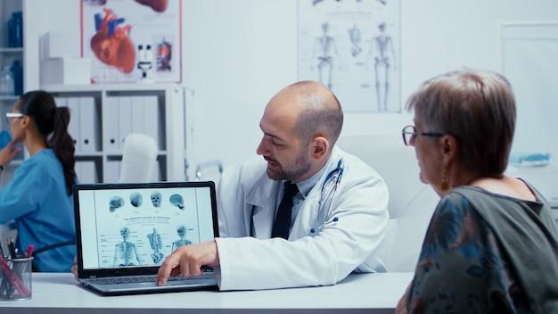 은퇴한 노부인에게 뼈 문제를 피하는 방법을 설명하는 젊은 남성 의사. 백그라운드에서 걷는 의료진이 있는 현대적인 개인 병원 또는 클리닉의 방사선 및 방사선 촬영, 간호사