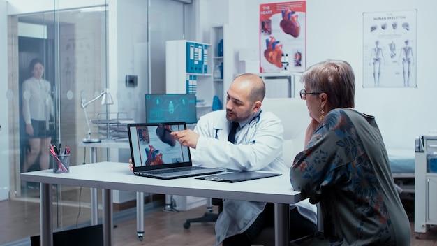 Молодой мужчина-врач объясняет возможную болезнь сердца пожилой пациентке на пенсии. проблемы с пороком сердца, представленные кардиологом-кардиологом, прикрепляют к сердцу. здравоохранение в современной частной клинике