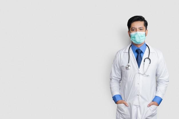 隔離された壁、健康概念上のコートのポケットにマスクと手で覆われた若い男性医師の顔