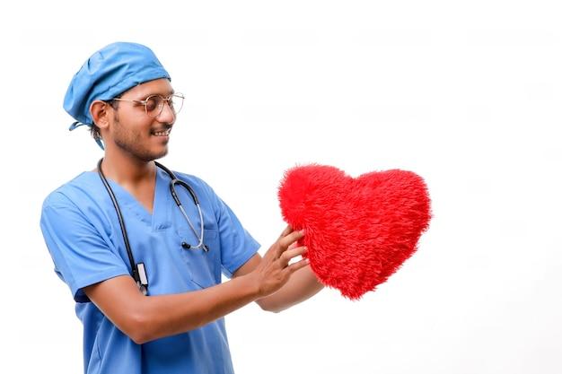手に美しい赤いハートの形を持っている若い男性医師