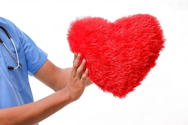 Молодой мужчина-врач держит в руке красивое красное сердце