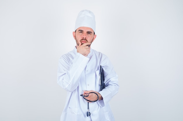 젊은 남성 의사 클립 보드, 청진기를 들고 흰색 유니폼과 사려 깊은 찾고 턱에 손을 유지. 전면보기.