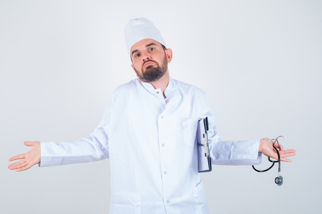 Young male doctor holding clipboard and stethoscope, showing helpless gesture by shrugging in white uniform and looking puzzled. front view.