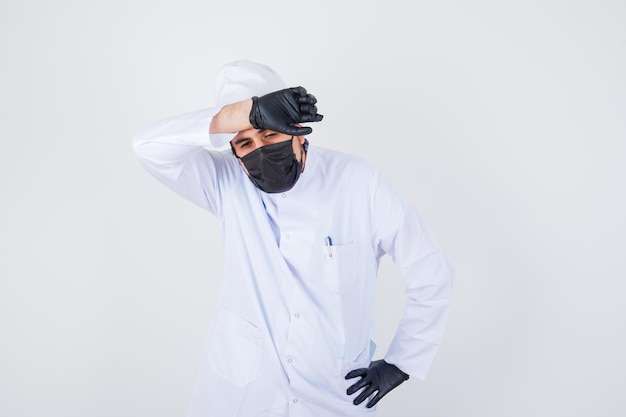Young male doctor holding hand on forehead in white uniform and looking fatigued , front view.