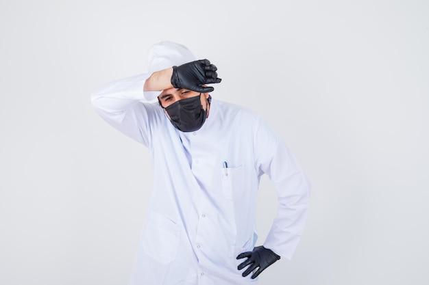 Молодой мужчина-врач держит руку на лбу в белой форме и выглядит утомленным, вид спереди.