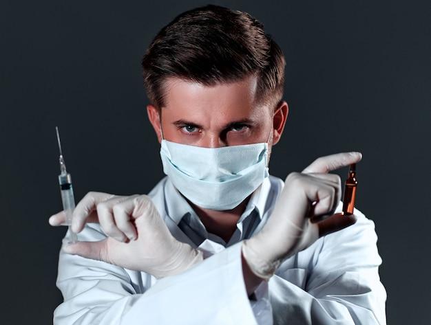 白衣と医療用マスクを身に着けた若い男性医師は、腕を組んでアンプルと注射器を持ち、黒で隔離されています。