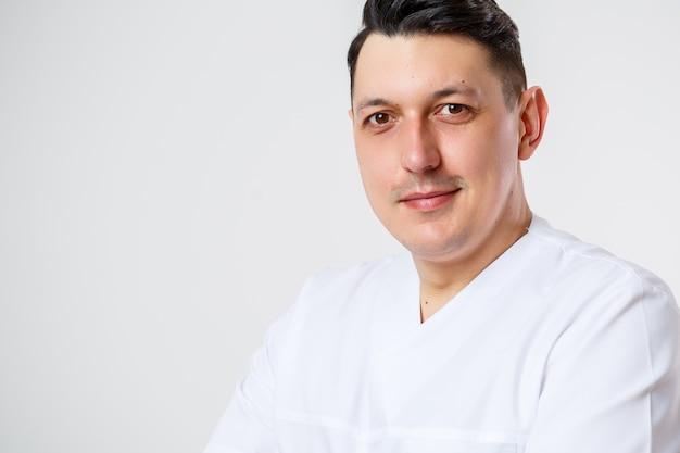 흰색 수술복을 입은 젊은 남성 의사. 흰색 배경에 격리됨