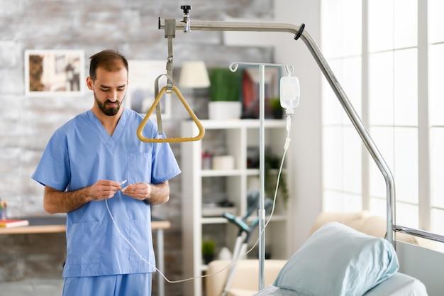 Молодой мужчина-врач в современном доме престарелых. современный объект.