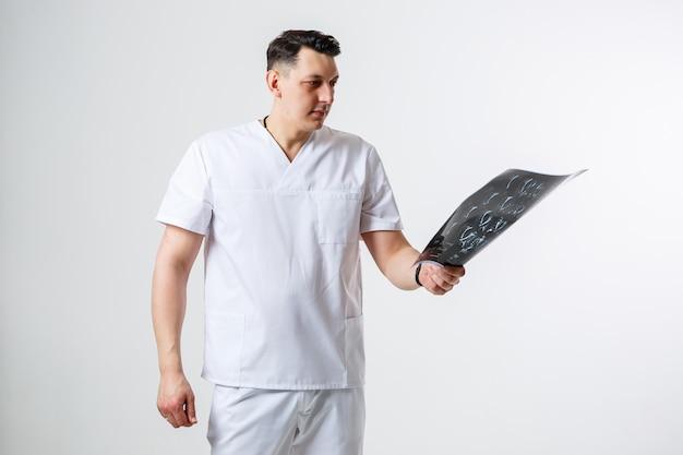 흰색 수술복을 입은 젊은 남성 의사가 환자 머리의 mri 스캔을 들고 검사합니다. 흰색 배경에 격리됨