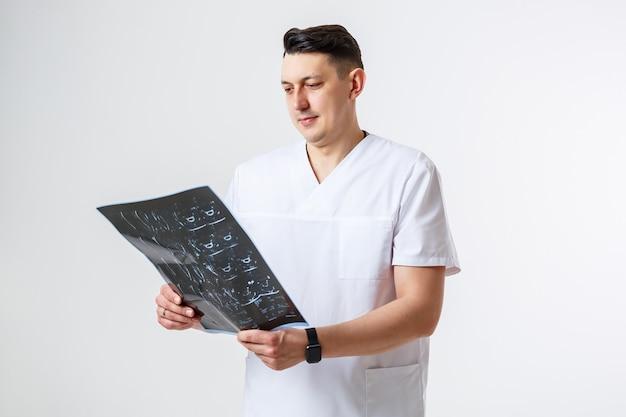 Молодой мужчина-врач в белом хирургическом костюме держит и исследует мрт головы пациента. изолированный на белом фоне