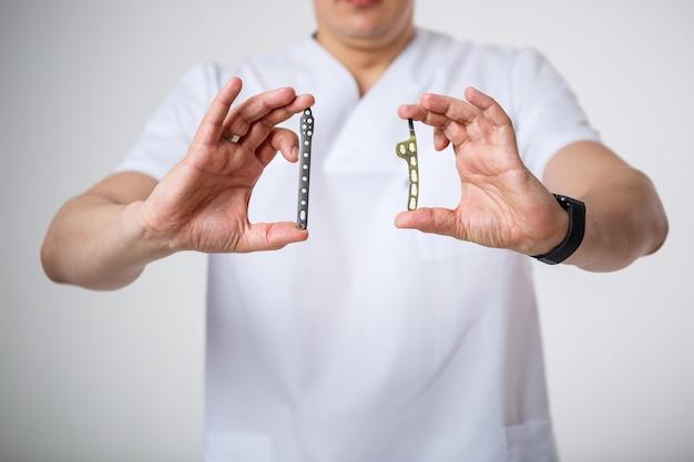 흰색 수술복을 입은 젊은 남성 의사는 골절 치료를 위해 티타늄 판을 잡고 검사합니다. 흰색 배경에 격리됨