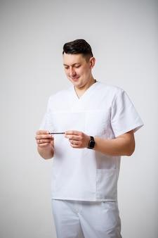 白い手術スーツの若い男性医師は、骨折治療のためにチタンプレートを保持し、検査します。白い背景で隔離