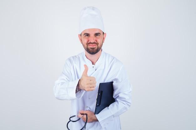 흰색 제복을 입은 젊은 남성 의사 클립 보드, 청진기를 들고 인사로 악수를 제공하고 부드러운, 전면보기를 찾고 있습니다.