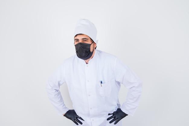 Молодой мужчина-врач в белой форме, взявшись за руки на талии и глядя задумчиво, вид спереди.
