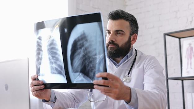 Молодой мужчина-врач смотрит на рентген грудной клетки, сидя в медицинском кабинете