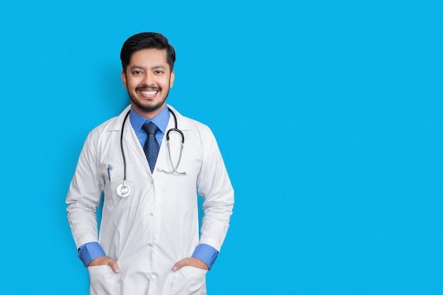 青い壁に隔離されたポケットに聴診器と腕で笑っている若い男性医師。健康保険の概念。
