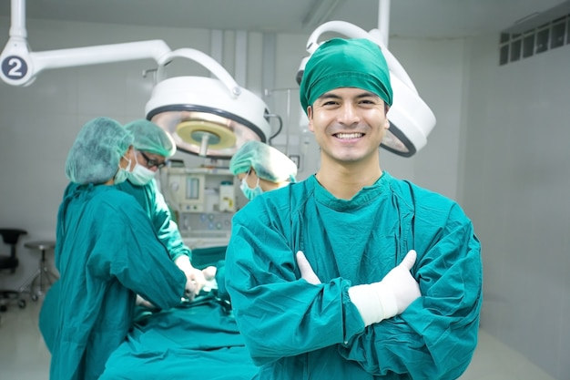 Young male doctor looking to camera with attractive smile at operating room background.