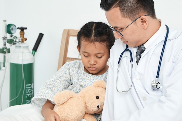 Young male doctor pediatrician checking girl