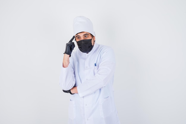 Young male doctor pointing head in white uniform and looking confident , front view.