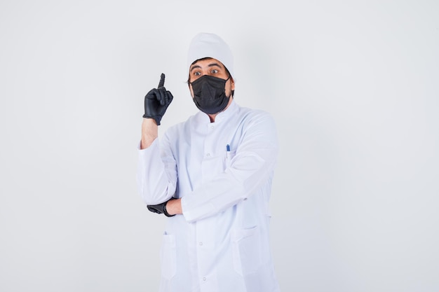 Young male doctor pointing up in white uniform and looking confident , front view.