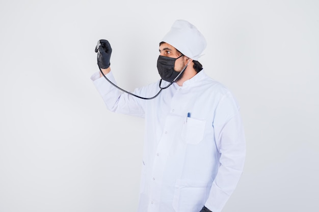 Young male doctor pretending to check beats in white uniform and looking confident , front view.