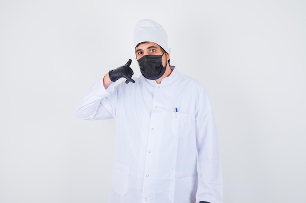 Young male doctor showing call me gesture in white uniform and looking confident. front view.
