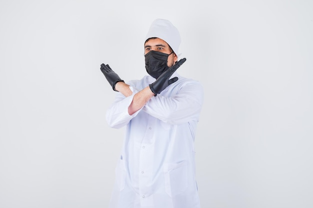 Young male doctor showing stop gesture in white uniform and looking confident , front view.