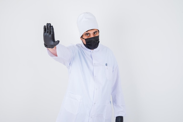 Young male doctor showing stop gesture in white uniform and looking confident. front view.