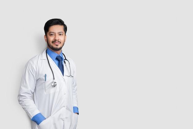 白い壁に隔離されたポケットに聴診器と腕で笑っている若い男性医師。健康保険の概念。