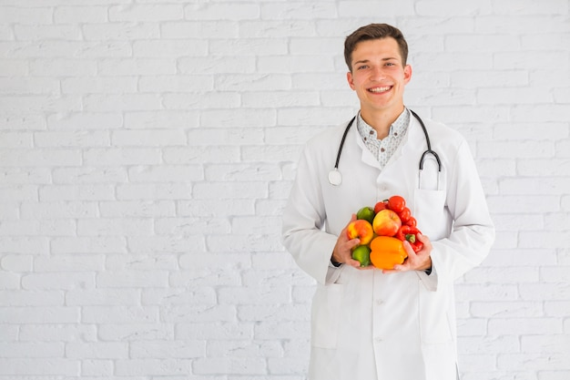 Young male doctor standing against the wall holding healthy food