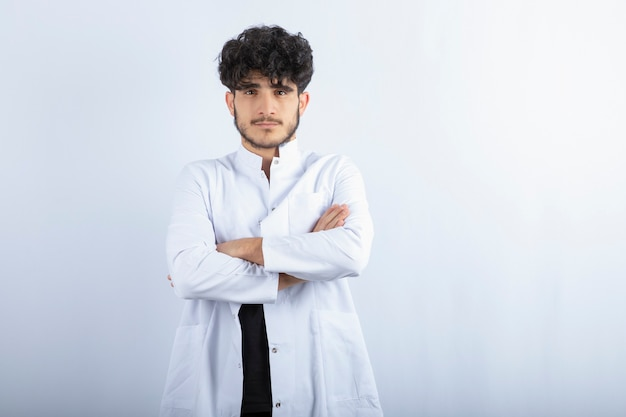 Giovane medico maschio in piedi sul muro bianco.