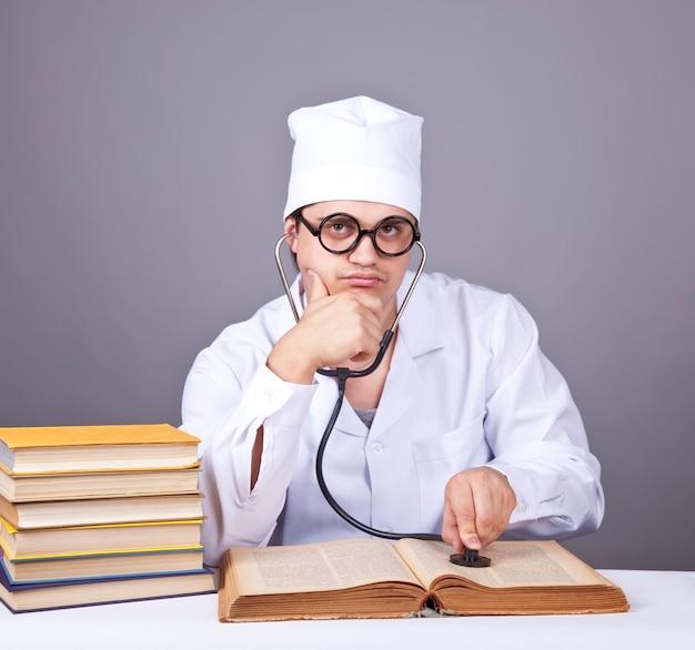 의료 책을 공부하는 젊은 남성 의사.