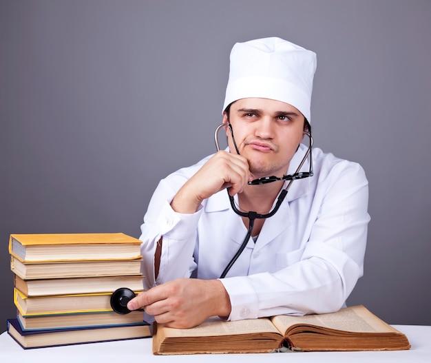 Молодой мужской доктор изучает медицинские книги.