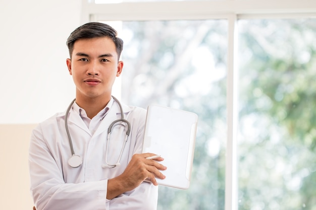 Young male doctor using tablet computer looking camera with white gown suite wearing stethoscope on neck for seaching information treating patients in hospital or clinic, healthcare medical concept