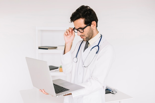 Young male doctor wearing eyeglasses looking at laptop screen